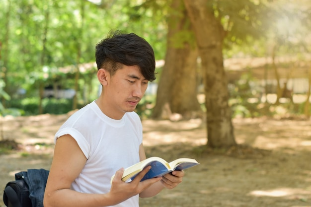 Portrait of young man reading a book in the park on summer day.
