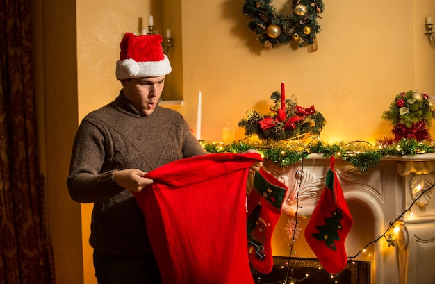 Portrait of young man in red hat looking inside of santa bag with amazement