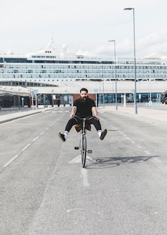 Portrait of young man riding bicycle on road with legs kicked out in front of cruise
