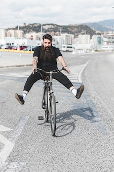 Portrait of young man riding bicycle on road with legs kicked out