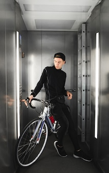 Portrait of a young man riding in the elevator along with a bicycle.