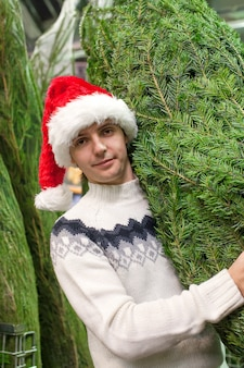Portrait of young man in santa hat buying christmas tree
