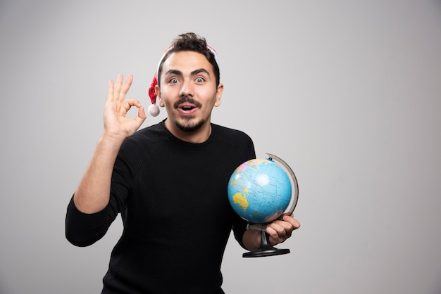 Portrait of a young man in santa's hat showing ok sign and holding a globe.