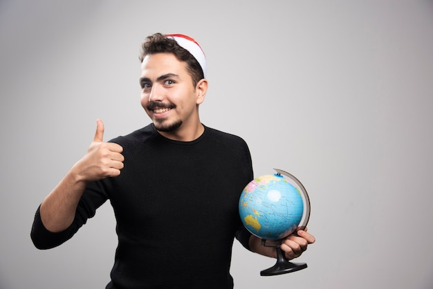 Portrait of a young man in santa's hat showing a thumb up and holding a globe.