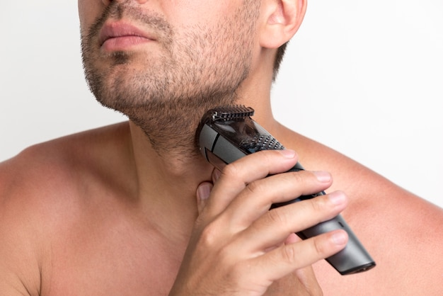 Portrait of young man shaving his beard with electric shaver