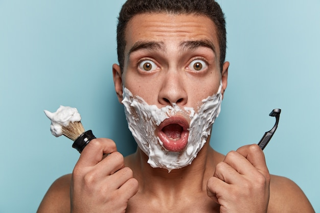 Portrait of young man shaving his beard