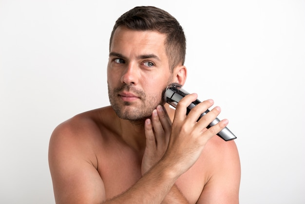 Portrait of young man shaving with trimmer against white background