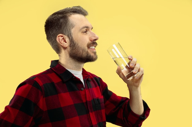 Portrait of young man in shirt drinking water