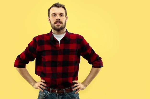 Ritratto di giovane uomo in camicia.vista frontale. colori alla moda. in piedi e sorridente.