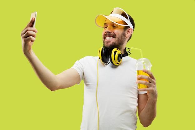 Ritratto di giovane uomo in camicia. modello maschile con cuffie e bevanda. le emozioni umane, l'espressione facciale, l'estate, il concetto di fine settimana. fare selfie.