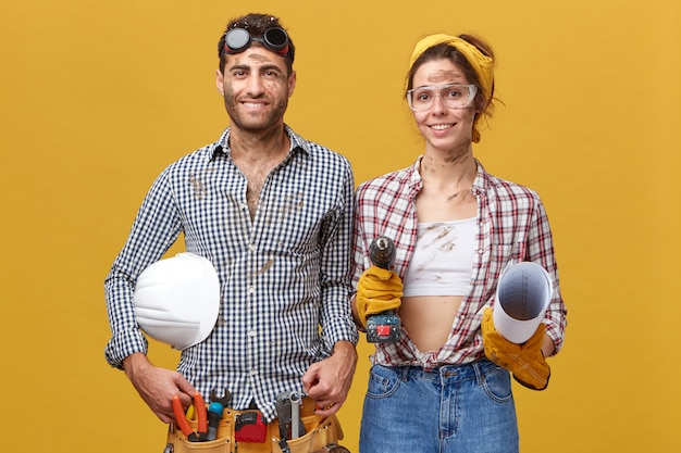 Portrait of young man in shirt and trousers having belt filled with tools and hardhat standing near her wife who helps him to fix things holding drilling machine and blueprint wearing shirt and jeans