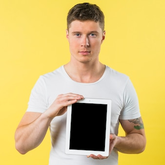 Portrait of a young man showing blank screen digital tablet against yellow backdrop