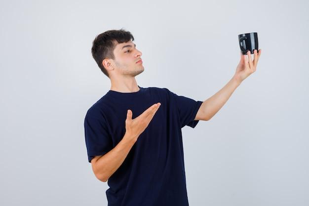 Ritratto di giovane uomo che mostra una tazza di tè in maglietta nera e guardando pensieroso vista frontale