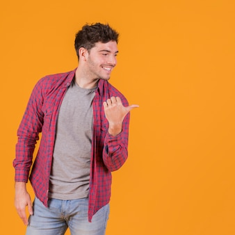 Portrait of a young man showing his thumb to side against an orange backdrop