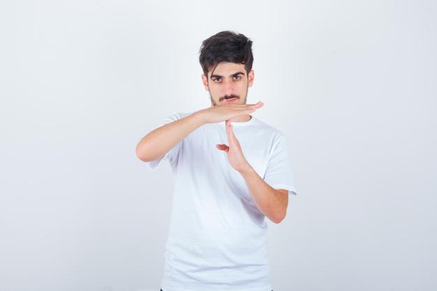 Ritratto di giovane uomo che mostra il gesto di timeout in maglietta e sembra fiducioso in vista frontale