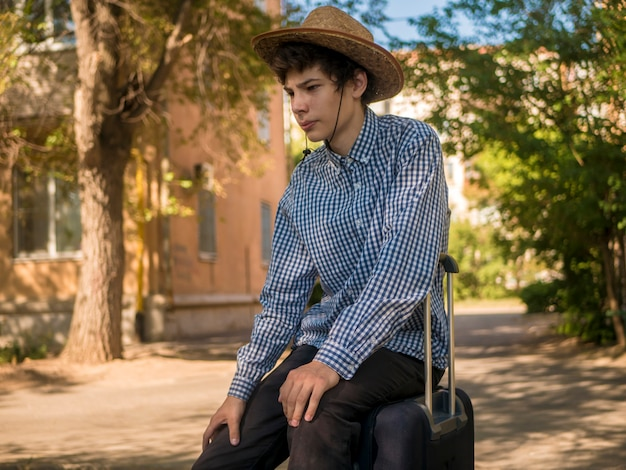 Portrait young man sit in baggage case walking in europe city street on a summer vacation