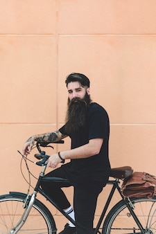Portrait of a young man sitting on bicycle looking at camera against beige wall