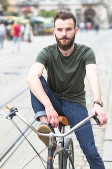 Portrait of a young man sitting on bicycle