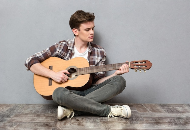Portrait of a young man sitting on the floor and playing on guitar on gray wall