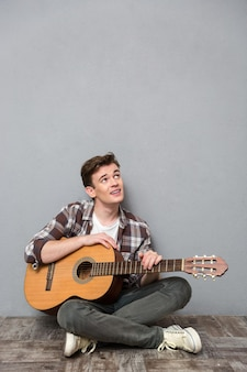 Portrait of a young man sitting on the floor with guitar and looking up at copyspace