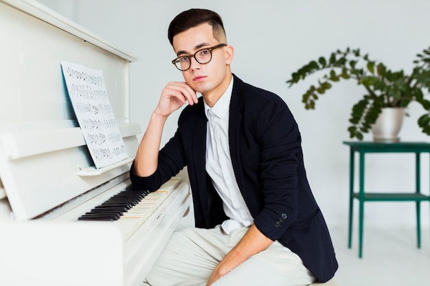Portrait of a young man sitting near the piano looking at camera