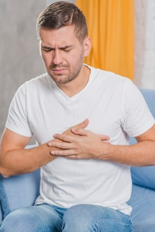 Portrait of a young man sitting on sofa having pain chest