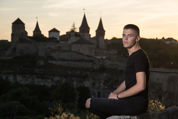 Portrait of a young man sitting on stone wall an ancient castle and sunset