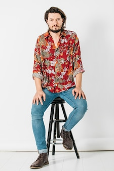 Portrait of a young man sitting on stool isolated on white background