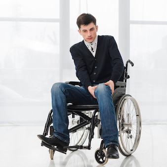 Portrait of a young man sitting on wheelchair having pain in his leg