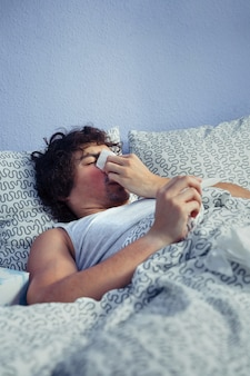Portrait of young man sneezing and covering nose with tissue while holding thermometer lying on bed. sickness and healthcare concept.
