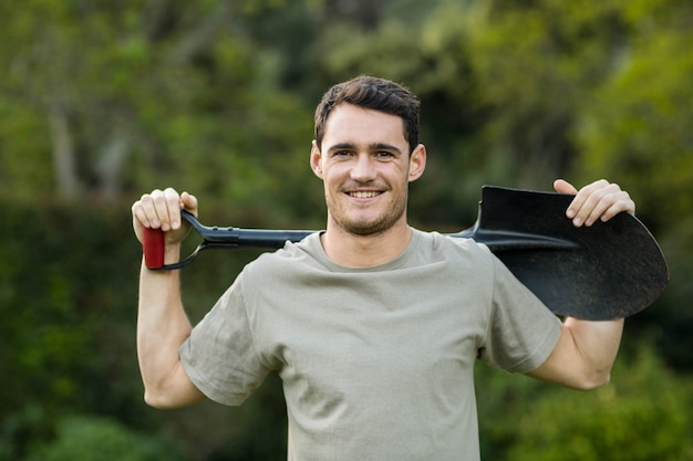 Portrait of young man standing in garden with a gardening shovel