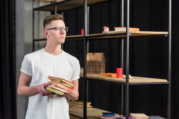 Portrait of a young man standing near the showcase holding colorful books in hand