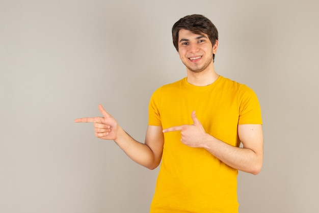 Portrait of a young man standing and showing thumb up against gray.