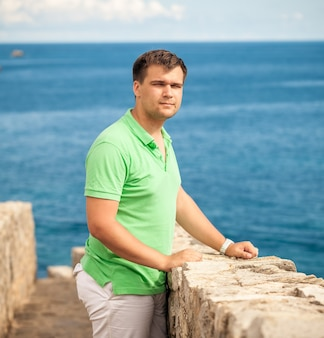 Portrait of young man standing on stone wall at seaside fortress