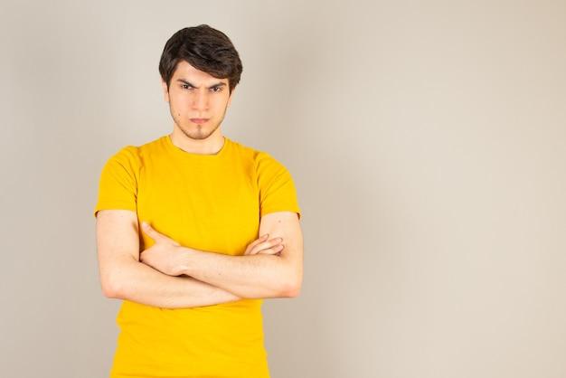 Ritratto di un giovane in piedi con le braccia incrociate contro il grigio.