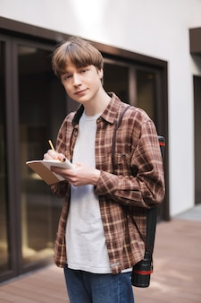 Portrait of young man standing with notebook and pencil in hands and dreamily