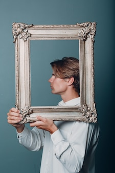 Portrait young man standing with picture frame at studio.