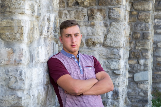 Portrait of young man on stone wall background