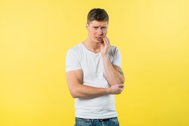 Portrait of a young man suffering from toothache against yellow background