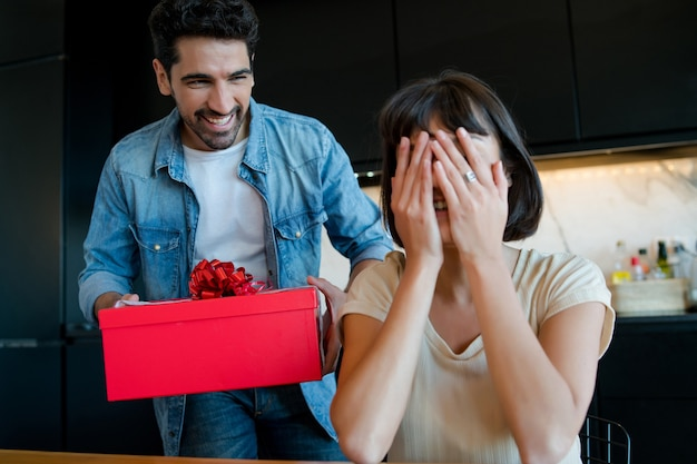 Portrait of young man surprising his girlfriend with a gift box