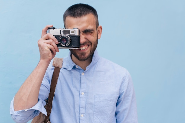 Portrait of young man taking picture with retro camera