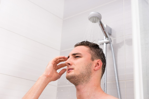 Portrait of young man taking a shower, standing under flowing water in shower cabin in the modern tiled bathroom