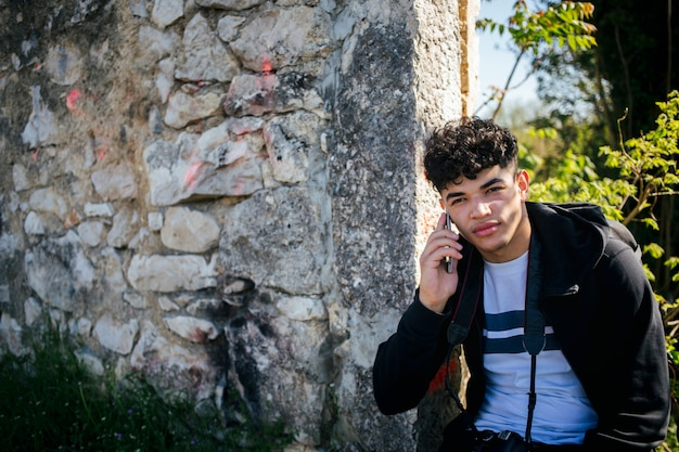 Portrait of young man talking on cellphone near stone wall