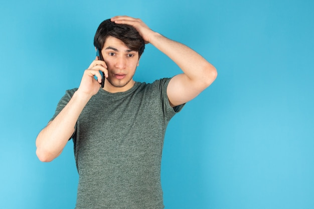 Portrait of a young man talking on mobile phone against blue.