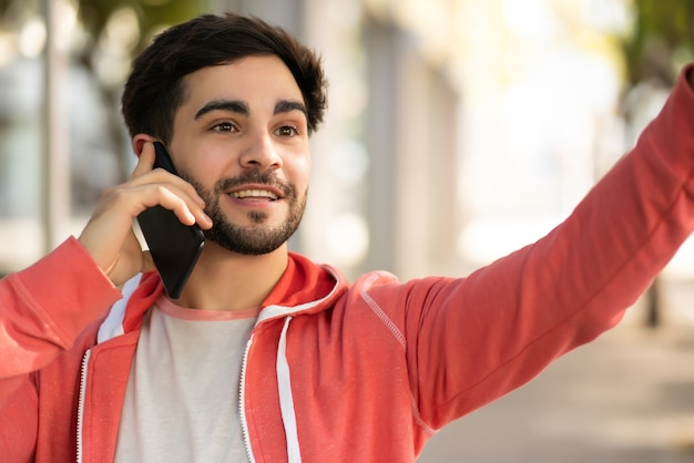 Portrait of young man talking on the phone and raising his hand to hail a taxi while standing outdoors on the street. urban concept.