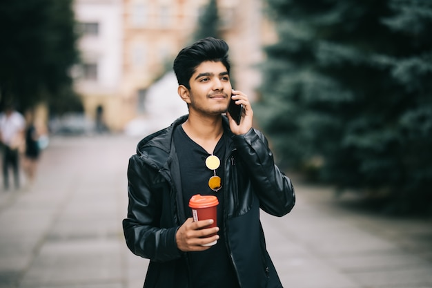 Portrait of young man talking on phone and walking on the street