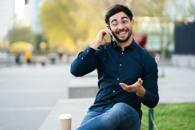 Portrait of young man talking on the phone while sitting on bench outdoors. urban concept.