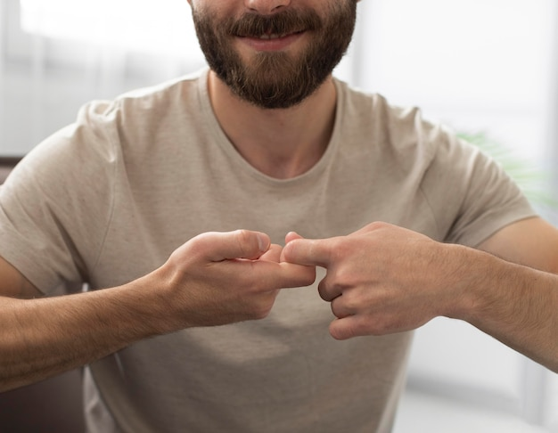 Portrait of young man teaching sign language