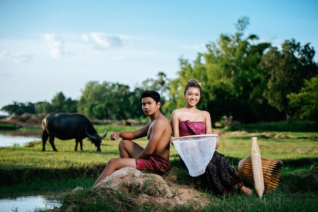 Portrait young man topless sitting near pretty woman in beautiful clothes in rural lifestyle, bamboo fishing trap
