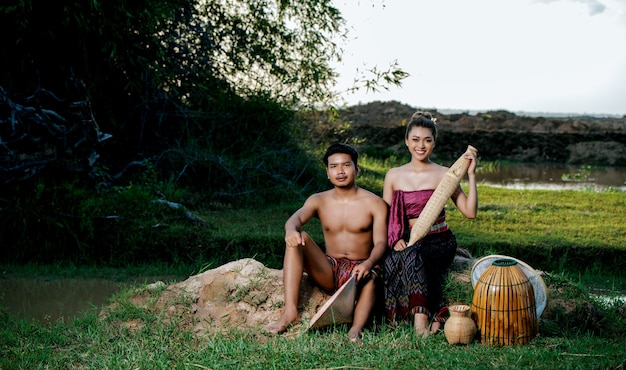 Portrait young man topless sitting near pretty woman in beautiful clothes in rural lifestyle